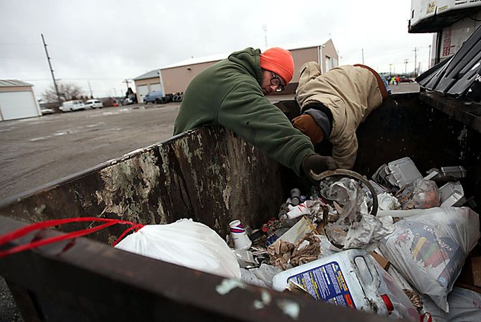 "Volunteers David Patterson, of Archbold, Ohio, left, and Matthew Poorman, of Swanton, Ohio, search a dumpster behind Hutches Towing as the search for 9-year-old Andrew, 7-year-old Alexander and 5-year-old Tanner Skelton continues in Holiday City, Ohio on Tuesday, Nov. 30, 2010. Authorities ""do not anticipate a positive outcome"" in the search for three Michigan brothers who have been missing since their father's attempted suicide, a police chief said Tuesday. (AP Photo/Detroit Free Press, Andre J. Jackson)"