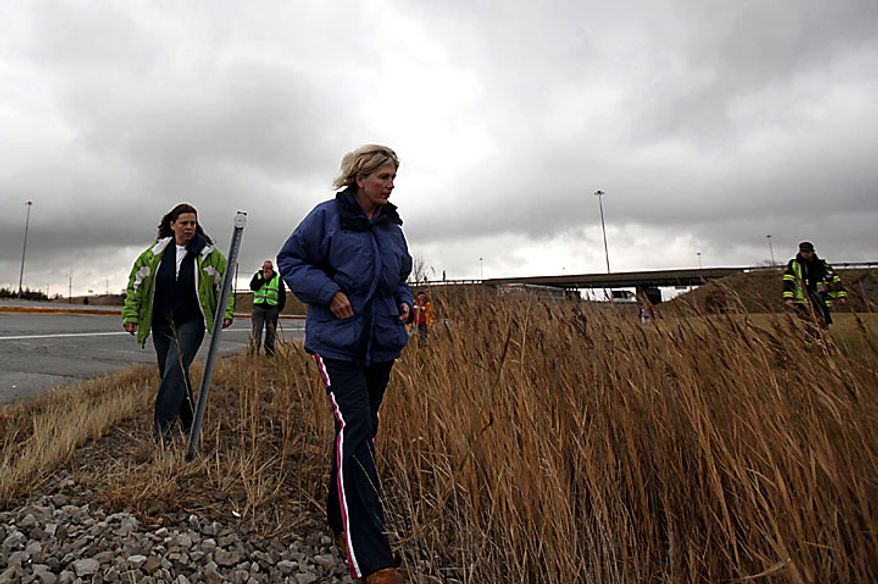 """Volunteers walk the Ohio Turnpike looking for clues as the search for 9-year-old Andrew, 7-year-old Alexander and 5-year-old Tanner Skelton continues in Holiday City, Ohio on Tuesday, Nov. 30, 2010. Authorities """"do not anticipate a positive outcome"""" in the search for three Michigan brothers who have been missing since their father's attempted suicide, a police chief said Tuesday. (AP Photo/Detroit Free Press, Andre J. Jackson)"""