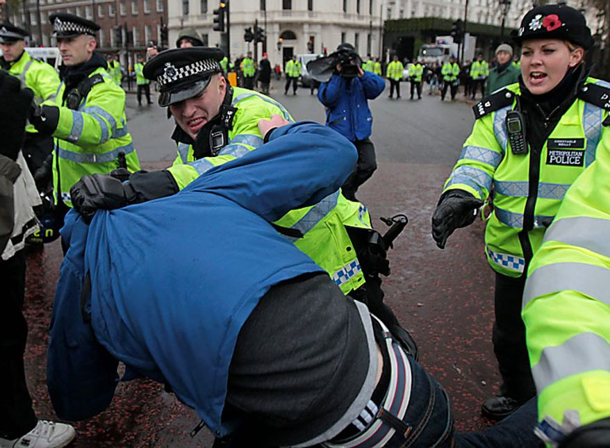 A British police officer scuffles with a protester during a march by a group of students outside Buckingham Palace, protesting against tuition fees increases in central London, Tuesday, Nov. 30, 2010. Thousands of British students protested Wednesday against government plans to triple university tuition fees. (AP Photo/Lefteris Pitarakis)