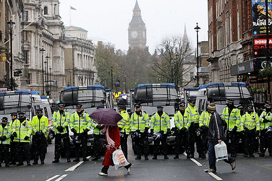 People walk past British police officers blocking off Whitehall leading to the Houses of Parliament in London as students march through the streets in a protest against tuition fees, Tuesday, Nov. 30, 2010. (AP Photo/Sang Tan)