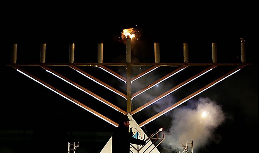 Russia's chief rabbi, Berel Lazar lights candles on the menorah during the lighting ceremony marking the start of Hanukkah outside the Kremlin in Moscow, Wednesday, Dec. 1, 2010. Dozens of people gathered in below-freezing temperatures outside the Kremlin to watch the lighting of the menorah. (AP Photo/Ivan Sekretarev)