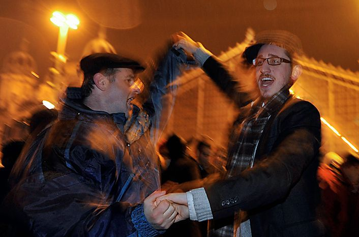 Members of the Hungarian Orthodox Jewish community dance at the beginning of the Hanukkah Festival in downtown Budapest, Hungary, Wednesday, Dec 1, 2010. The Hanukkah Festival,  also known as the Festival of Lights, is lasting eight days  and it's commemorating the rededication of the Second Temple in 165 BC at the time of the Maccabee rebellion. (AP Photo/Bela Szandelszky)