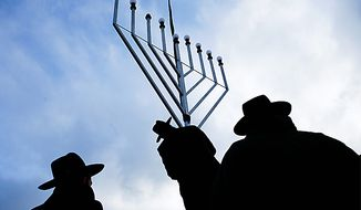 Rabbi Yehuda Teichtal, center, installs with other Rabbis a giant Hanukkah Menorah at the launch of the eight-day Jewish Festival of Lights, named Hanukkah, at the Pariser Platz near the Brandenburg Gate in central Berlin on Wednesday, Dec. 1, 2010. (AP Photo/Markus Schreiber)