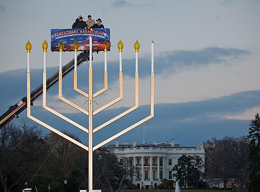 Rabbi Abraham Shemtov, left, Office of Management and Budget director Jacob Lew, center, and Rabbi Levi Shemtov light the National Menorah in celebration of Hanukkah on Wednesday, Dec. 1, 2010, in Washington.  (AP Photo/Evan Vucci)