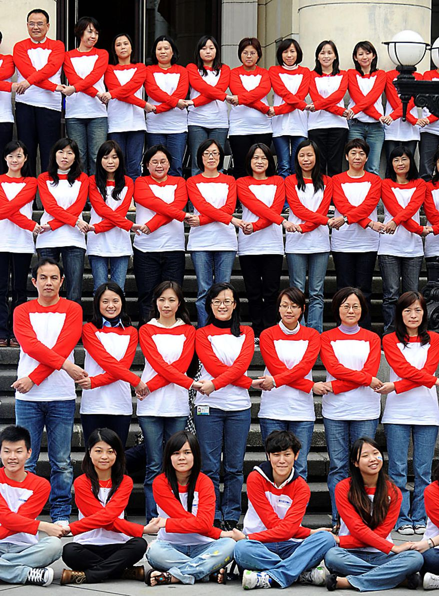 """In this photo relased by China's Xinhua News Agency, some 100 """"campus ambassadors of AIDS prevention"""" pose to form the shapes of red ribbons during an activity in Taipei, Taiwan, on Tuesday, Nov. 30, 2010, a day ahead of the World AIDS Day. (AP Photo/Xinhua, Wong Ching-teng)"""