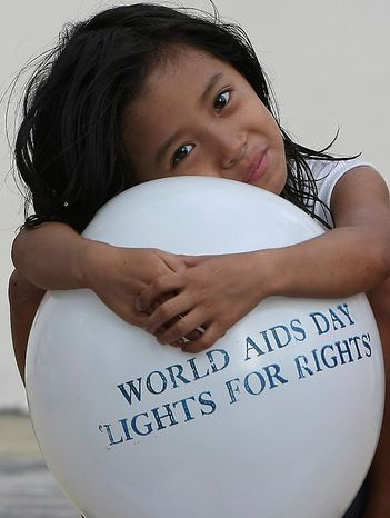 A little girl embraces a balloon as Filipino health workers and volunteers, not in the photo, mark World AIDS Day in Manila, Philippines Wednesday, Dec. 1, 2010. Citing 2008 figures, WHO (World Health Organization) said some 33.4 million are living with HIV, with 2.7 million newly infected with the virus and 2 million dying of AIDS. The Philippines has a low prevalence of HIV infection with 5,729 cases, according to the data from the Department of Health. (AP  Photo/Bullit Marquez)