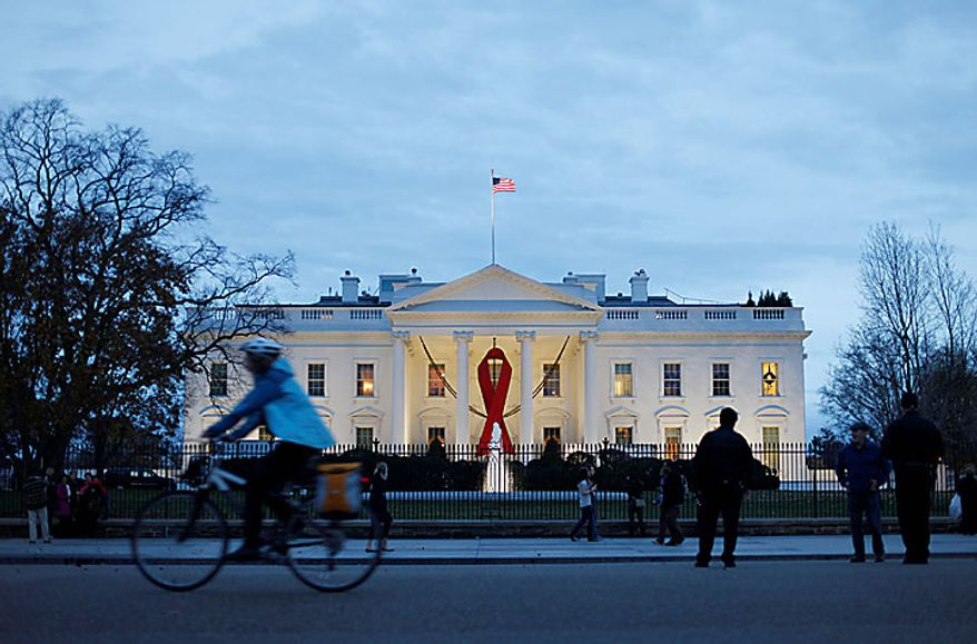A red ribbon hangs from the the North Portico of the White House in Washington, Tuesday, Nov., 30, 2010, to commemorate World Aids Day.(AP Photo/Pablo Martinez Monsivais)