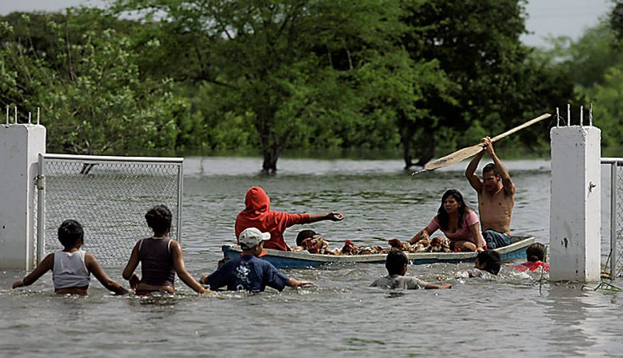 """People rescue chickens from a flooded chicken farm in Palmira, southern Colombia, Tuesday, Nov. 30, 2010.  According to meteorologists the """"La Nina"""" climatic phenomenon is causing an exceptionally wet rainy season that has caused floods and landslides, killing over 130 people throughout Colombia. (AP Photo/Christian Escobar Mora)"""
