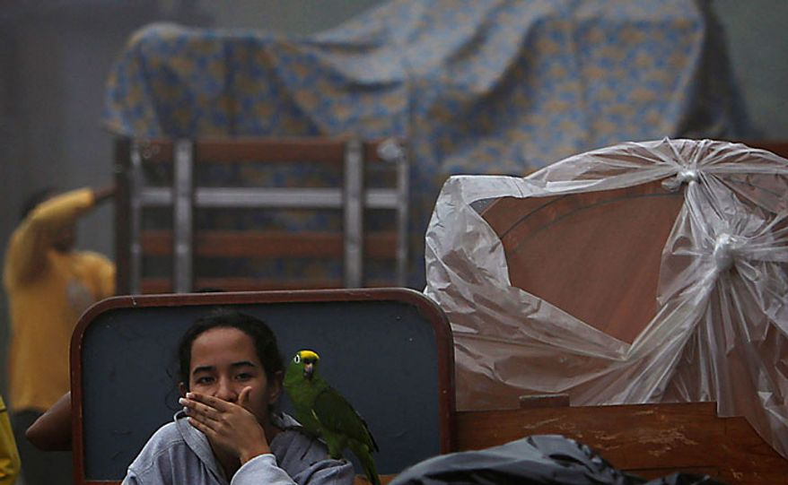 A woman sits with her belongings and her bird as she evacuates from her home after nearby homes fell due to heavy rain in Caracas, Venezuela, Tuesday Nov. 30, 2010. Flooding and landslides unleashed by torrential rains have killed at least 30 people in Venezuela, forced thousands from their homes and idled an oil refinery.  (AP Photo/Fernando Llano)
