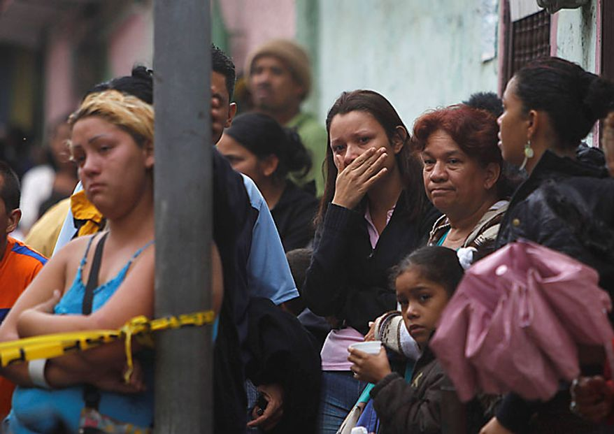 People watch rescue efforts after homes fell due to heavy rain in Caracas, Venezuela, Tuesday Nov. 30, 2010.  Flooding and landslides unleashed by torrential rains have killed at least 30 people in Venezuela, forced thousands from their homes and idled an oil refinery. (AP Photo/Fernando Llano)