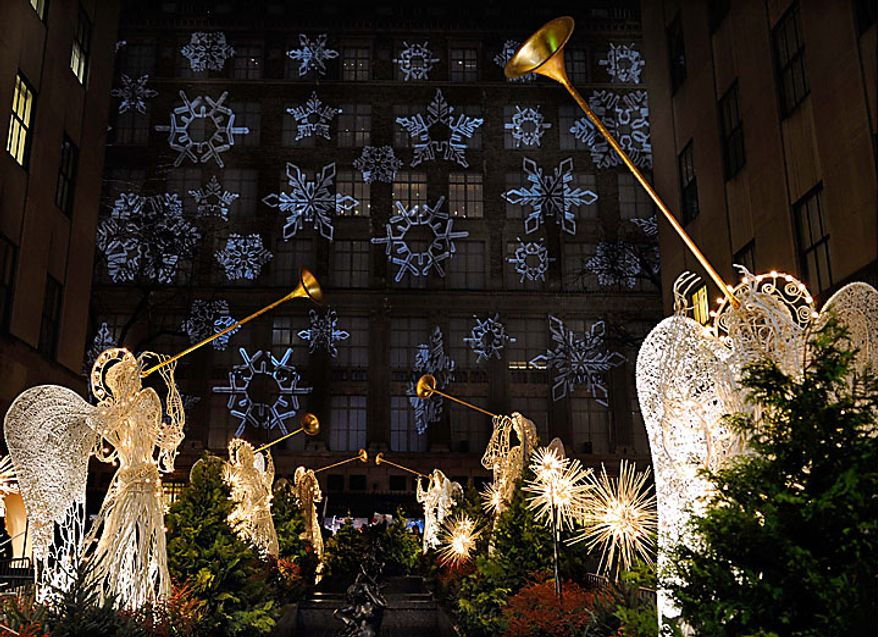 Angels in the Channel Gardens are lighted as light is reflected off Saks Fifth Avenue store  across Fifth Avenue  during the Rockefeller Center Christmas  78th annual lighting ceremony Tuesday, Nov. 30 , 2010 in New York. (AP Photo/Stephen Chernin)