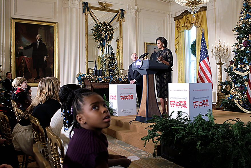 First lady Michelle Obama stands with retired Marine Lt. Gen. Pete Osman as she speaks about the Toys for Tots program which distributes gifts to needy children, Wednesday, Dec. 1, 2010, in the East Room of the White House in Washington. (AP Photo/Charles Dharapak)