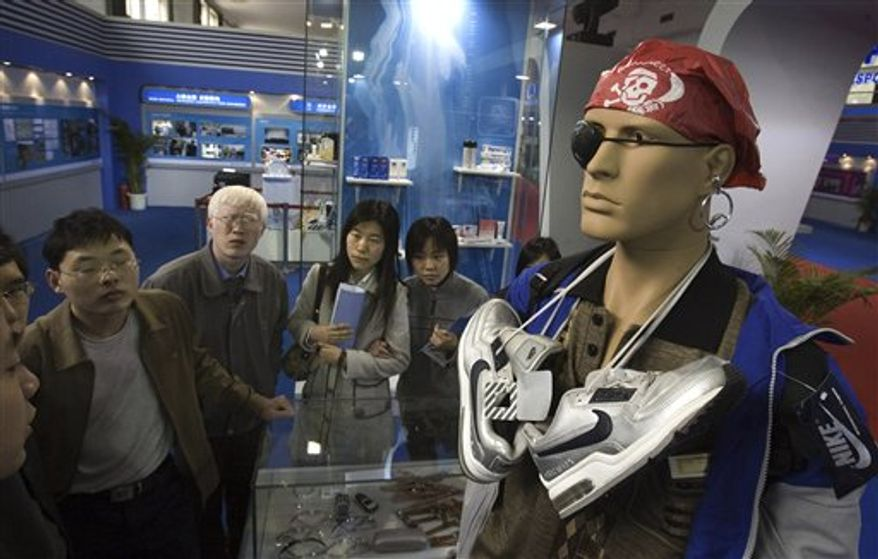 FILE - In this April 17, 2006 file photo, visitors walk past a mannequin set up to show how individuals attempt to get past customs, smuggling counterfeit products in violation of intellectual property rights law during an exhibition in Beijing. China's government announced a new crackdown Tuesday, Nov. 30, 2010 on rampant illegal copying of products from software to music that is adding to tensions with Washington and other governments over trade and currency complaints. (AP Photo/Ng Han Guan, File)