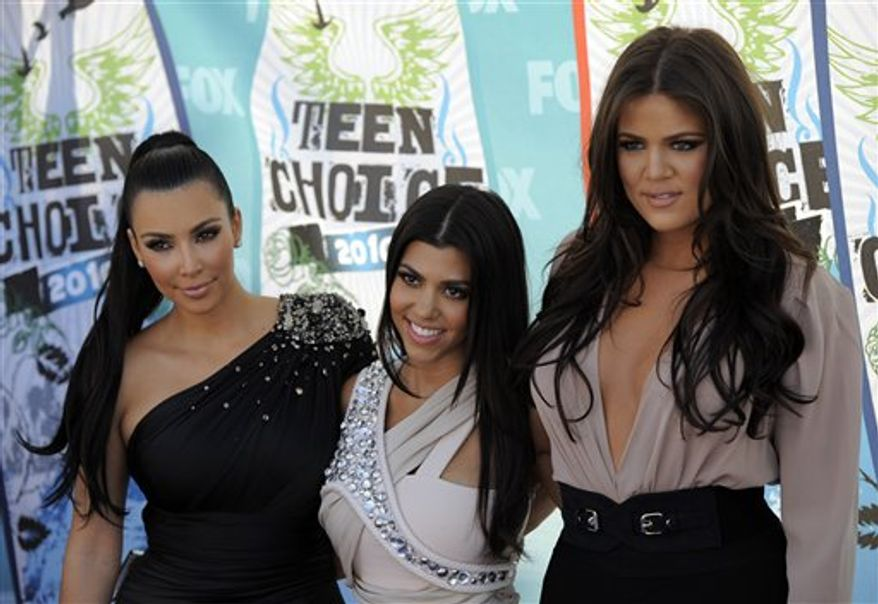 FILE - In this Aug. 8, 2010 file photo, from left, Kim Kardashian, Kourtney Kardashian and Khloe Kardashian arrive at the Teen Choice Awards in Universal City, Calif. The Kardashian sisters are seeking to cut ties with a venture that sold prepaid debit cards under their name after coming under attack for the card's high fees. (AP Photo/Chris Pizzello, File)