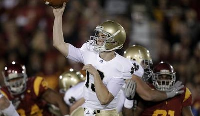 Southern California running back Marc Tyler, center, carries the ball as he is defended by Notre Dame linebackers Manti Te'o, left, and Brian Smith during the first half of an NCAA college football game in Los Angeles, Saturday, Nov. 27, 2010. (AP Photo/Jae C. Hong)