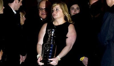 Line Burns carries an urn containing the remains of her late husband, former NHL coach Pat Burns, following his funeral in Montreal, Monday, Nov. 29, 2010. (AP Photo/The  Canadian Press,Graham Hughes)