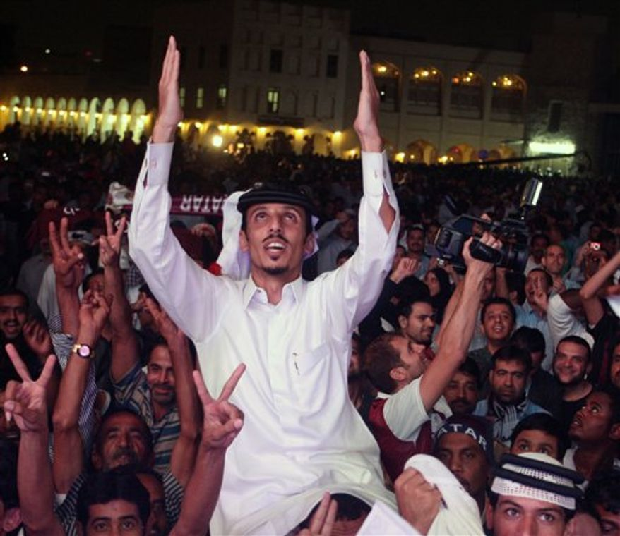 A girl celebrates in the Qatari capital Doha after the tiny Gulf state was chosen to host the 2022 World Cup on Dec. 2, 2010. Qatar became the first Arab, Middle Eastern or Muslim country to be awarded the right to stage football's World Cup Nov. 30, 2010 (AP Photo/Osama Faisal)