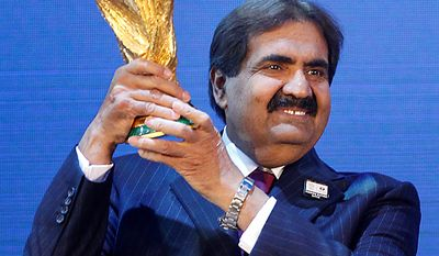 Sheikh Hamad bin Khalifa Al-Thani, Emir of Qatar, holds the World Cup trophy after the announcement of Qatar hosting the 2022 soccer World Cup in Zurich, Switzerland, Thursday, Dec. 2, 2010. (AP Photo/Michael Probst)
