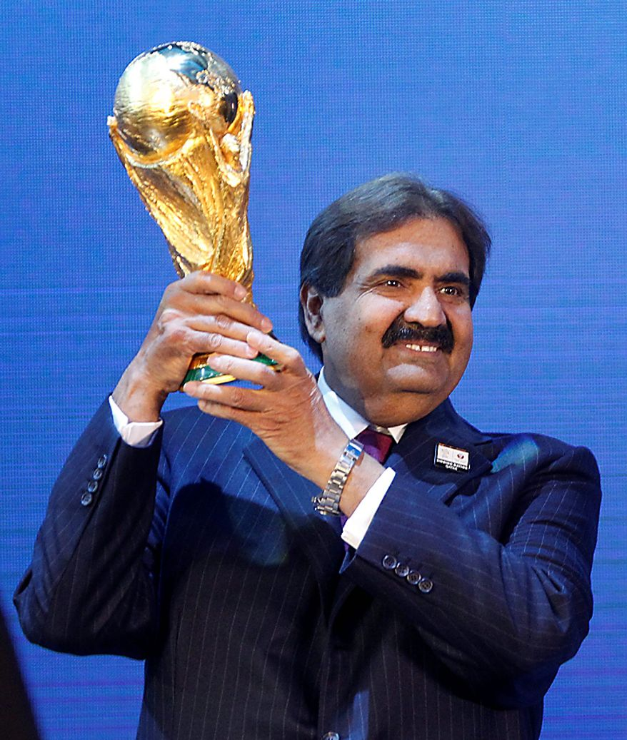 Sheikh Hamad bin Khalifa Al-Thani, Emir of Qatar, holds the World Cup trophy after the announcement of Qatar hosting the 2022 soccer World Cup in Zurich, Switzerland, Thursday, Dec. 2, 2010. (AP Photo/Michael Probst)