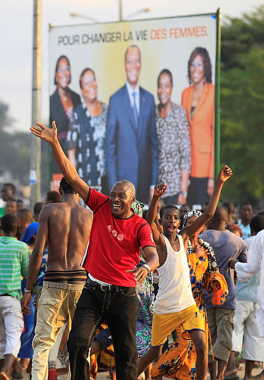 "Supporters of opposition leader Alassane Ouattara celebrate near one of his campaign posters in the streets after the electoral commission announced his victory in last Sunday's presidential runoff, in the Abobo neighborhood of Abidjan, Ivory Coast, on Thursday, Dec. 2, 2010.  A senior advisor to Ivory Coast President Laurent Gbagbo has described the announcement of the victory for the opposition as ""an attempted coup."" (AP Photo/Rebecca Blackwell)"
