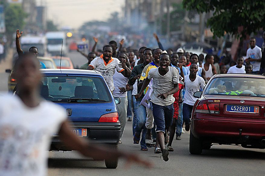 Supporters of opposition leader Alassane Ouattara run through the streets in celebration after the electoral commission head announced Mr. Ouattara's victory in last Sunday's presidential runoff, in the Abobo neighborhood of Abidjan, Ivory Coast, on Thursday, Dec. 2, 2010. (AP Photo/Rebecca Blackwell)