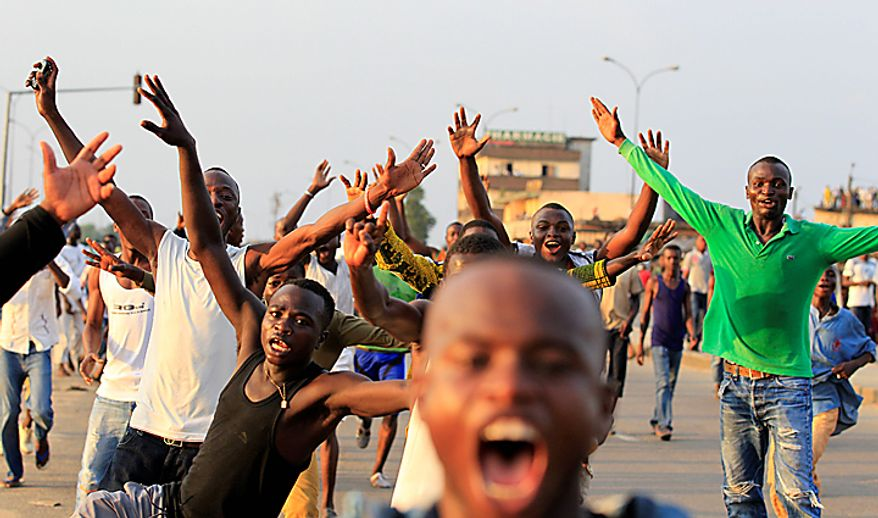 Supporters of opposition leader Alassane Ouattara celebrate in the streets after the electoral commission head announced Mr. Ouattara's victory in last Sunday's presidential runoff, in the Abobo neighborhood of Abidjan, Ivory Coast, on Thursday, Dec. 2, 2010. (AP Photo/Rebecca Blackwell)