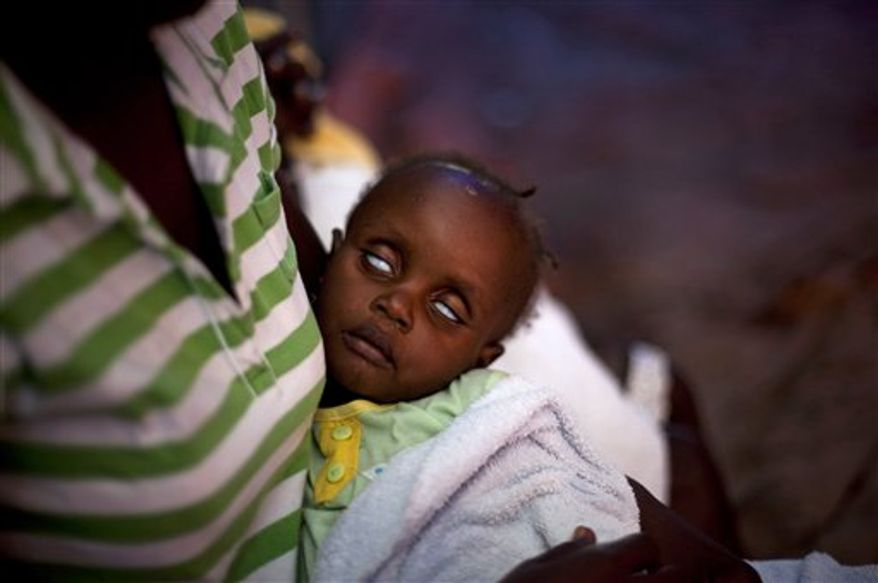 In this photo taken Nov. 27, 2010, Laika Valcoure, a 16-month-old suffering cholera symptoms, is held by her mother at a local hospital in Limbe near Cap Haitien, Haiti. Haiti's countryside is seeing the worst of an epidemic that has killed at least 1,800 people since erupting less than two months ago. (AP Photo/Emilio Morenatti)
