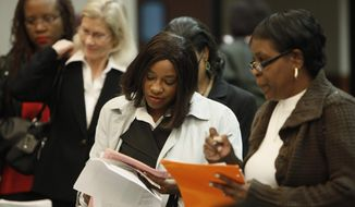 In this Nov. 10, 2010, photo, job seeker Stephanie Taylor, second from right, fills out an application while attending a job fair in Livonia, Mich. The nation's unemployment rate climbed to 9.8 percent in November, a seven-month high, as hiring slowed. (AP Photo/Paul Sancya)