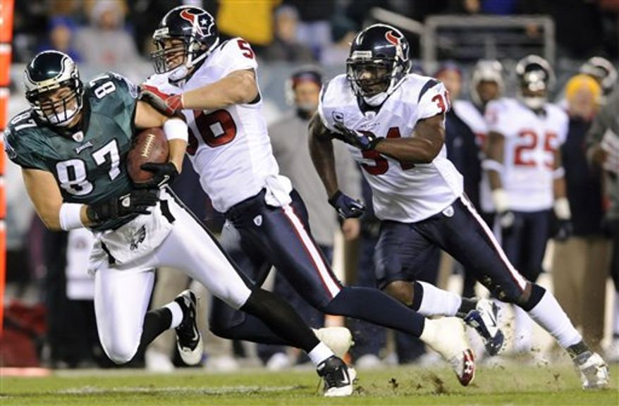 Philadelphia Eagles' Brent Celek (87) is brought down after a catch by Houston Texans' Brian Cushing (56) as Bernard Pollard (31) closes in during the first half of an NFL football game Thursday, Dec. 2, 2010, in Philadelphia. (AP Photo/Michael Perez)