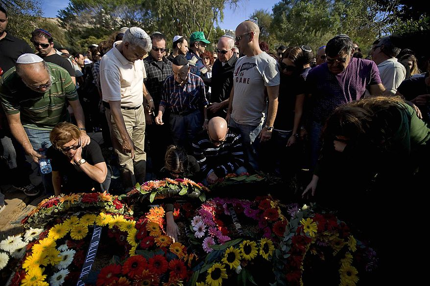 Israelis gather around the grave of Eran Weizel, killed when a wildfire in northern Israel set a bus alight which was carrying Israeli prison guards heading to rescue Palestinian inmates at a nearby prison, at the military cemetery in Haifa, Friday, Dec. 3, 2010. Foreign firefighters and aircraft poured into Israel Friday in an unprecedented wave of international assistance as the country battled a huge forest fire that has killed dozens of people and displaced thousands. (AP Photo/Oded Balilty)