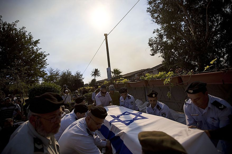Prison guards carry the coffin of Eran Weizel, killed when a wildfire in northern Israel set a bus alight which was carrying Israeli prison guards heading to rescue Palestinian inmates at a nearby prison, at the military cemetery in Haifa, Friday, Dec. 3, 2010. Foreign firefighters and aircraft poured into Israel Friday in an unprecedented wave of international assistance as the country battled a huge forest fire that has killed dozens of people and displaced thousands. (AP Photo/Oded Balilty)