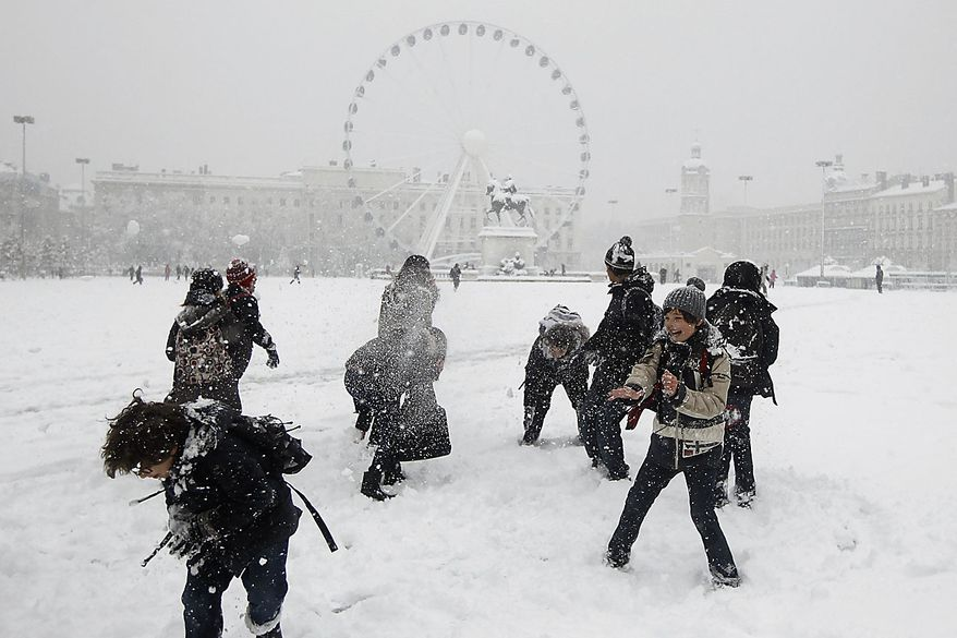 Children react during a snowball fight in Lyon, central France, Wednesday, Dec. 1, 2010. Heavy snow and subzero temperatures swept across Europe, killing at least eight homeless people in Poland, closing major airports in Britain and Switzerland, and causing delays to rail and road traffic across the continent. (AP Photo/Laurent Cipriani)