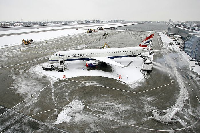 A British Airways plane is seen parked as staff clear snow on the runways to reopen the airport at the London City Airport in London, Thursday, Dec. 2, 2010. More heavy snow caused havoc across Britain on Thursday, keeping Gatwick airport closed for a second day, disrupting rail services and leaving travelers stranded. Commuters struggled to get to work as Britain's worst early winter weather in almost two decades showed no sign of easing its icy grip.(AP Photo/Akira Suemori)