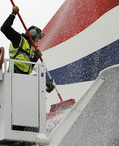 A member of staff clears snow on a British Airways plane to be ready for reopening the airport at the London City Airport in London, Thursday, Dec. 2, 2010. More heavy snow caused havoc across Britain on Thursday, disrupting rail services and leaving travellers stranded. Commuters struggled to get to work as Britain's worst early winter weather in almost two decades showed no sign of easing its icy grip.(AP Photo/Akira Suemori)