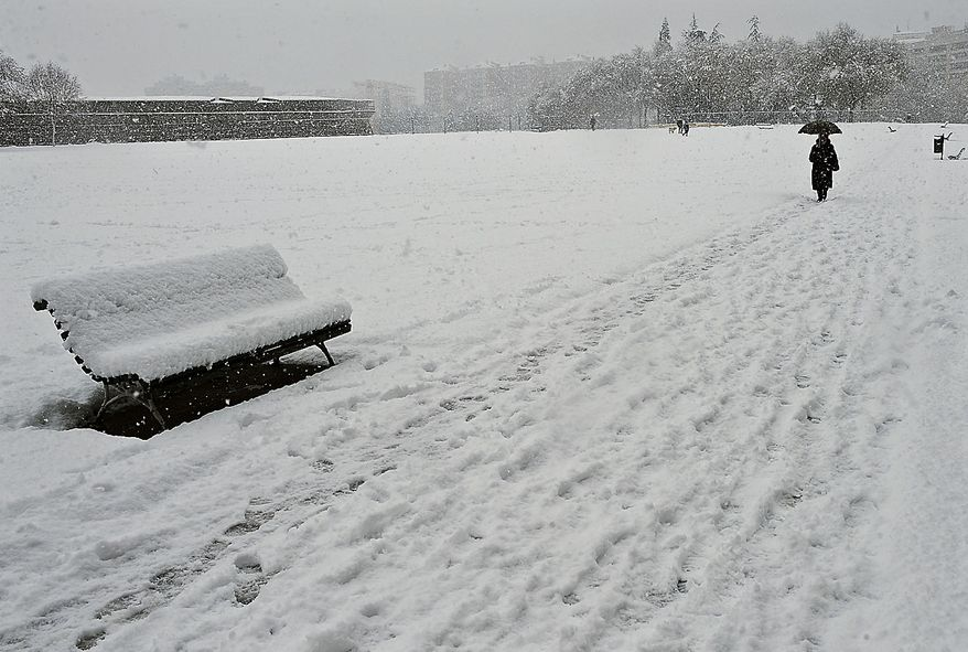 A person walk in Vuelta Castillo Park as snow covering the field and decorates the trees in Pamplona northern Spain, Friday Dec. 3, 2010. A polar wind is crossing the country as many parts of Spain registered freezing temperatures and snow storms. (AP Photo/Alvaro Barrientos)