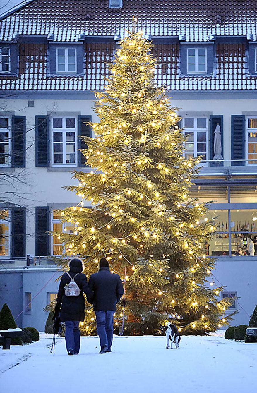 A couple with a dog walking towards an illuminated Christmas tree in front of a manor house in Gelsenkirchen, western Germany, Wednesday, Dec. 1, 2010.  Germany faces ice cold temperatures and snow.  (AP Photo/Martin Meisner)