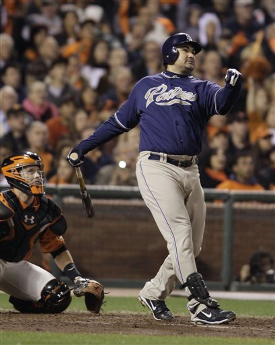 FILE - This Oct. 1, 2010, file photo shows San Diego Padres' Adrian Gonzalez hitting a three-run homer off San Francisco Giants starting pitcher Matt Cain during the third inning of their baseball game in San Francisco.  At left is San Francisco Giants catcher Buster Posey. Gonzalez has flown to Boston to take a physical exam needed to complete a trade from the San Diego Padres to the Red Sox, a person familiar with the situation told The Associated Press on Saturday, Dec. 4, 2010. (AP Photo/Eric Risberg, FILE)