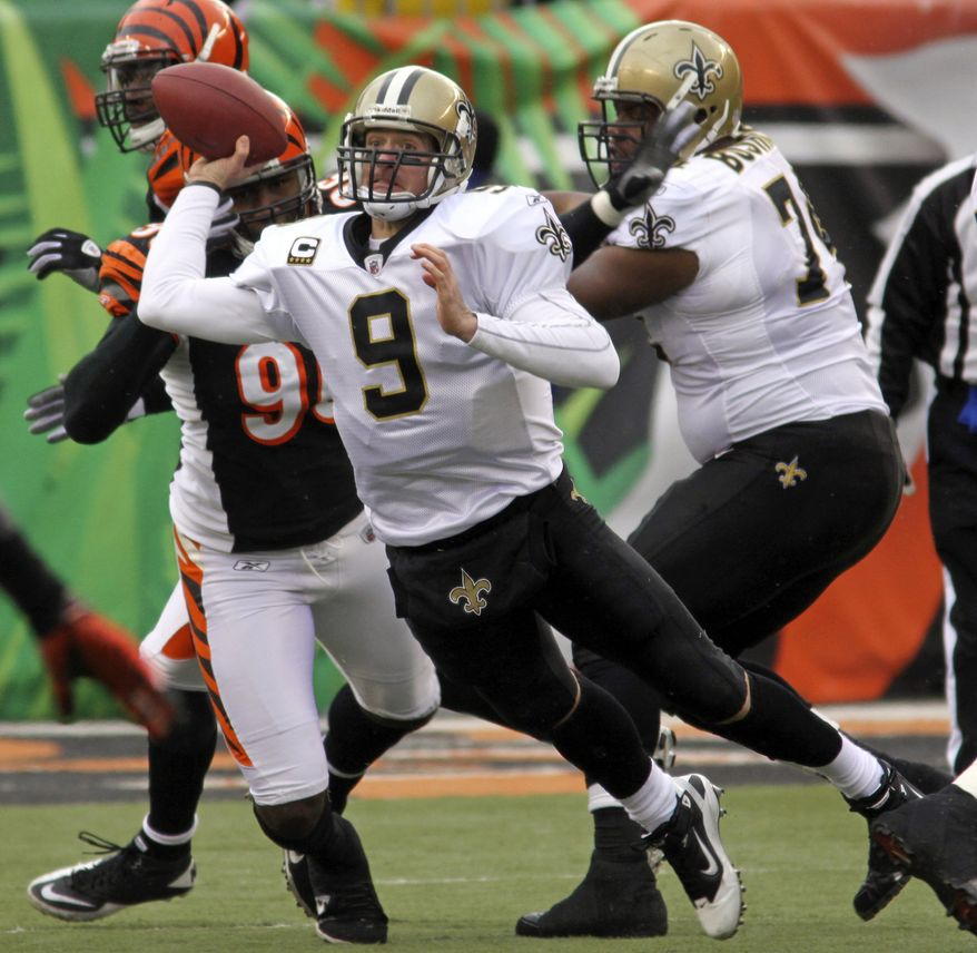 New Orleans Saints quarterback Drew Brees (9) gets a pass off under pressure from Cincinnati Bengals defensive end Carlos Dunlap, left, in the first half of an NFL football game, Sunday, Dec. 5, 2010, in Cincinnati. Offensive tackle Jermon Bushrod blocks at right. (AP Photo/Tom Uhlman)