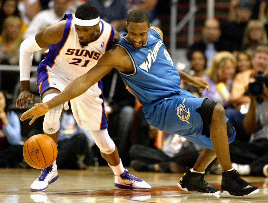 Phoenix Suns forward Hakim Warrick (21) and Washington Wizards guard Gilbert Arenas (9) battle for a loose ball during the second quarter of an NBA basketball game, Sunday, Dec. 5, 2010, in Phoenix. (AP Photo/Ralph Freso)