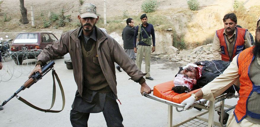 Pakistani volunteers rush an injured person into a local hospital in Peshawar on Monday. A pair of suicide bombers disguised as policemen killed as many as 50 people and wounded an estimated 100 in an attack targeting a tribal meeting called to discuss the formation of an anti-Taliban militia in Pakistani tribal area of Mohmand. (Associated Press)