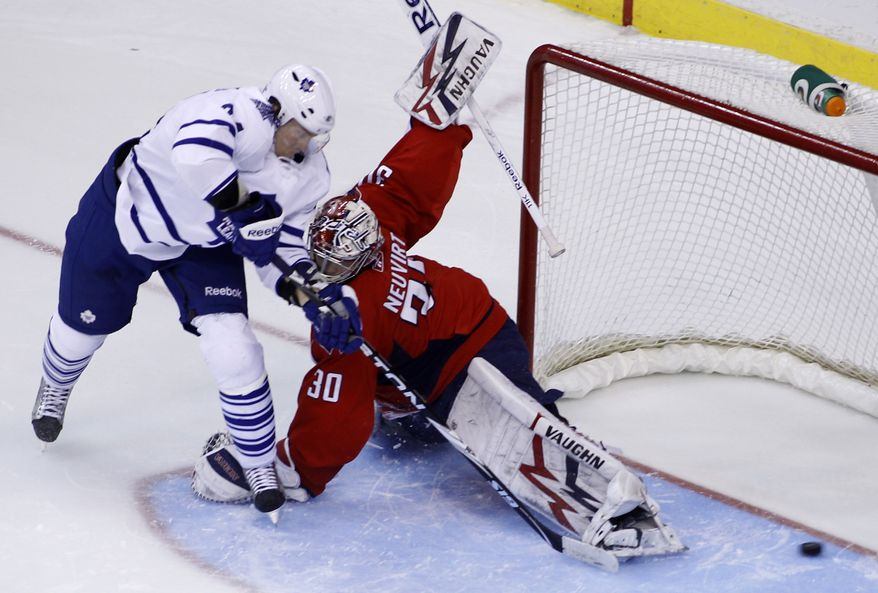 Toronto Maple Leafs' Mikhail Grabovski, left, of Germany, shoots the puck past Washington Capitals goalie Michal Neuvirth (30), of the Czech Republic, during a shootout of an NHL hockey game Monday, Dec. 6, 2010, in Washington. The Maple Leafs won 5-4 in a shootout. (AP Photo/Luis M. Alvarez)