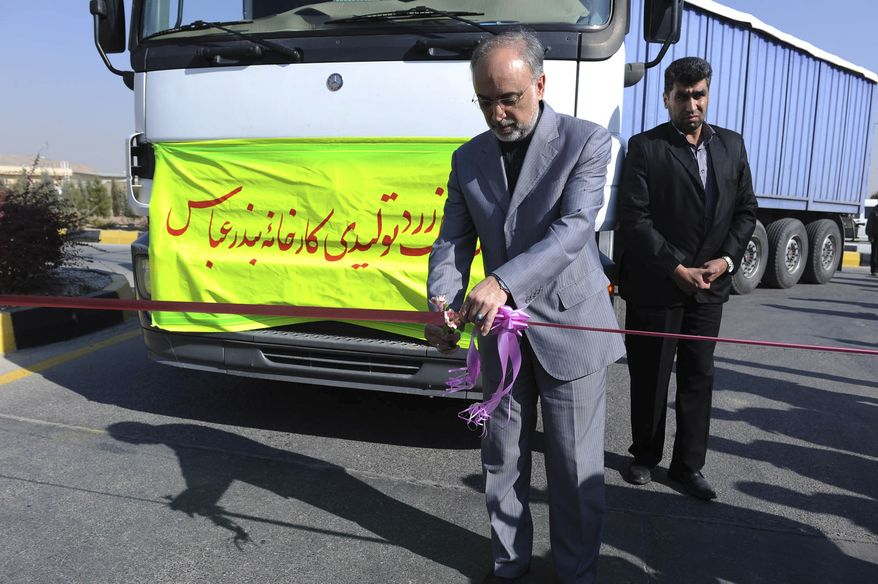 """Head of the Atomic Energy Organization of Iran, Ali Akbar Salehi, cuts a ribbon during a ceremony, as a truck is seen behind him, containing Iran's first domestically mined raw uranium, at the Isfahan uranium conversion facility in central Iran, Sunday, Dec. 5, 2010. Iran announced Sunday that it has delivered its first domestically mined raw uranium to a processing facility, claiming it is now self-sufficient over the entire nuclear fuel cycle. The translation reads """"First shipment of yellowcake produced in Bandar Abbas mill"""". (AP Photo/Mehr News Agency, Ehsan Khosravi)"""