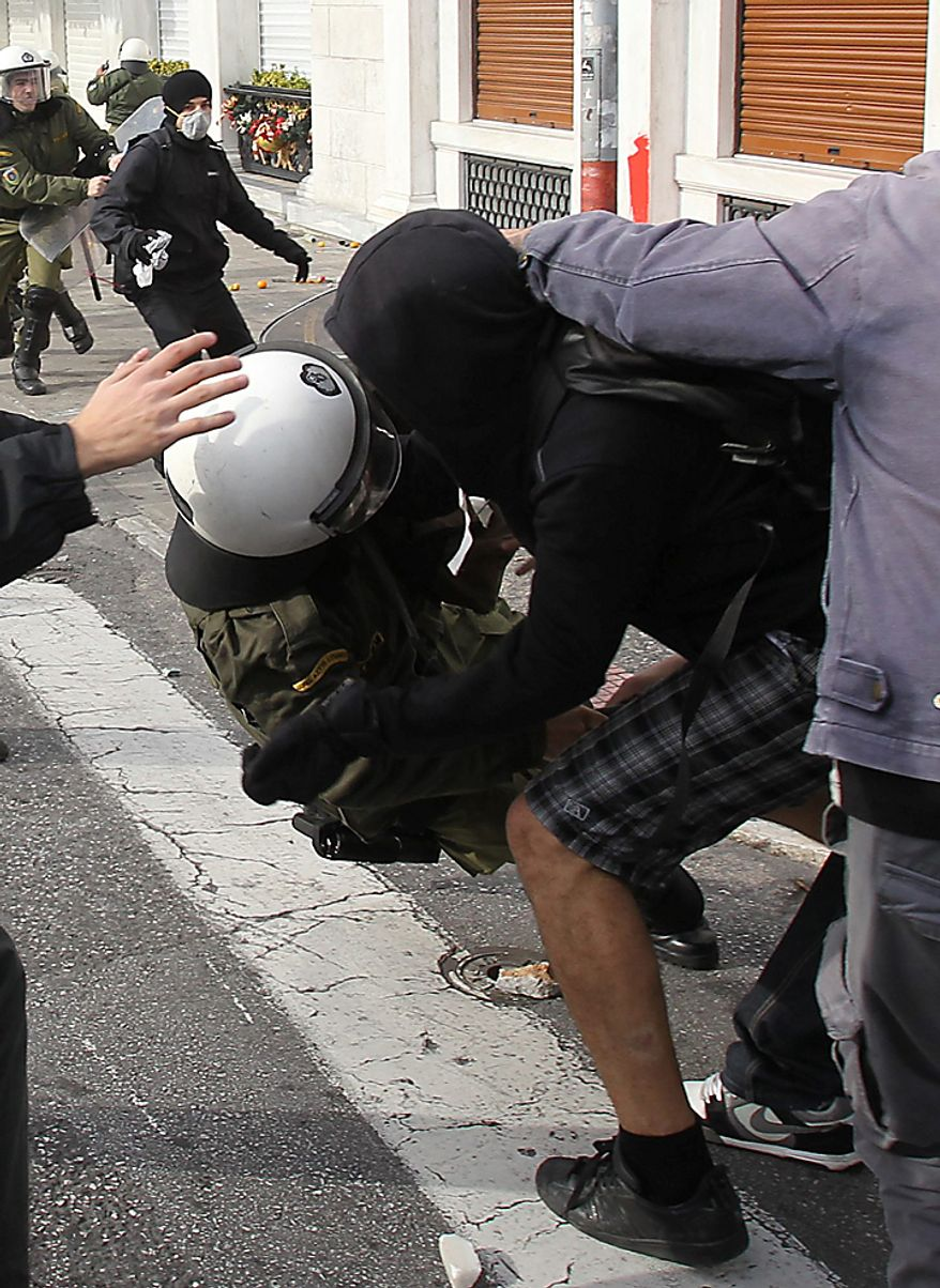 A youth attacks a riot policeman during a rally in Athens on Monday, Dec. 6, 2010. Youths hurled rocks and oranges at a government building in central Athens during a student protest to mark two years since the fatal police shooting of a teenage boy that sparked Greece's worst riots in decades. Police closed roads and deployed several thousand officers around the city but maintained a minimal presence at the site where some 1,500 students gathered outside Athens University's main buildings. (AP Photo/Thanassis Stavrakis)