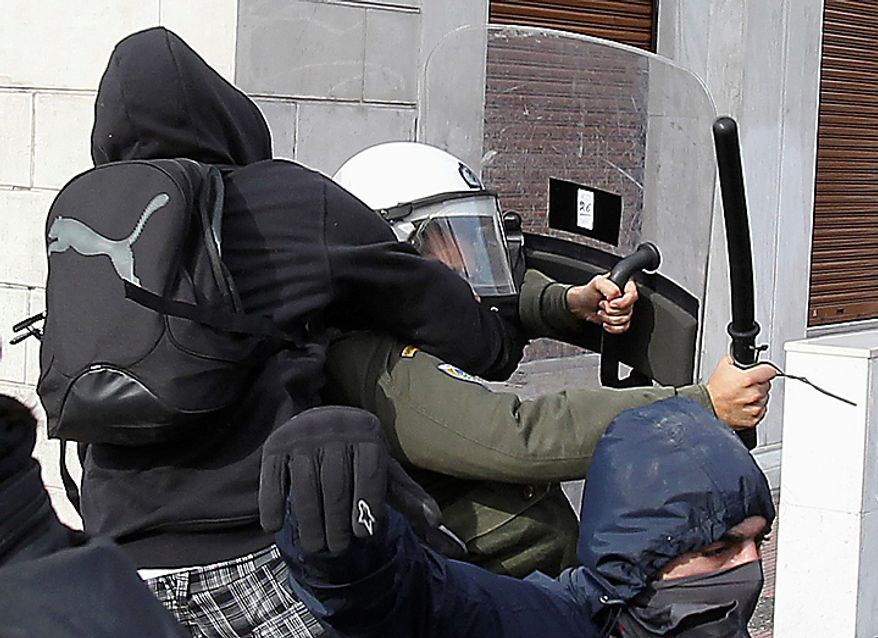 A youth with a bag attacks a riot policeman during a rally in Athens on Monday, Dec. 6, 2010. Youths hurled rocks and oranges at a government building in central Athens during a student protest to mark two years since the fatal police shooting of a teenage boy that sparked Greece's worst riots in decades. Police closed roads and deployed several thousand officers around the city but maintained a minimal presence at the site where some 1,500 students gathered outside Athens University's main buildings. (AP Photo/Thanassis Stavrakis)