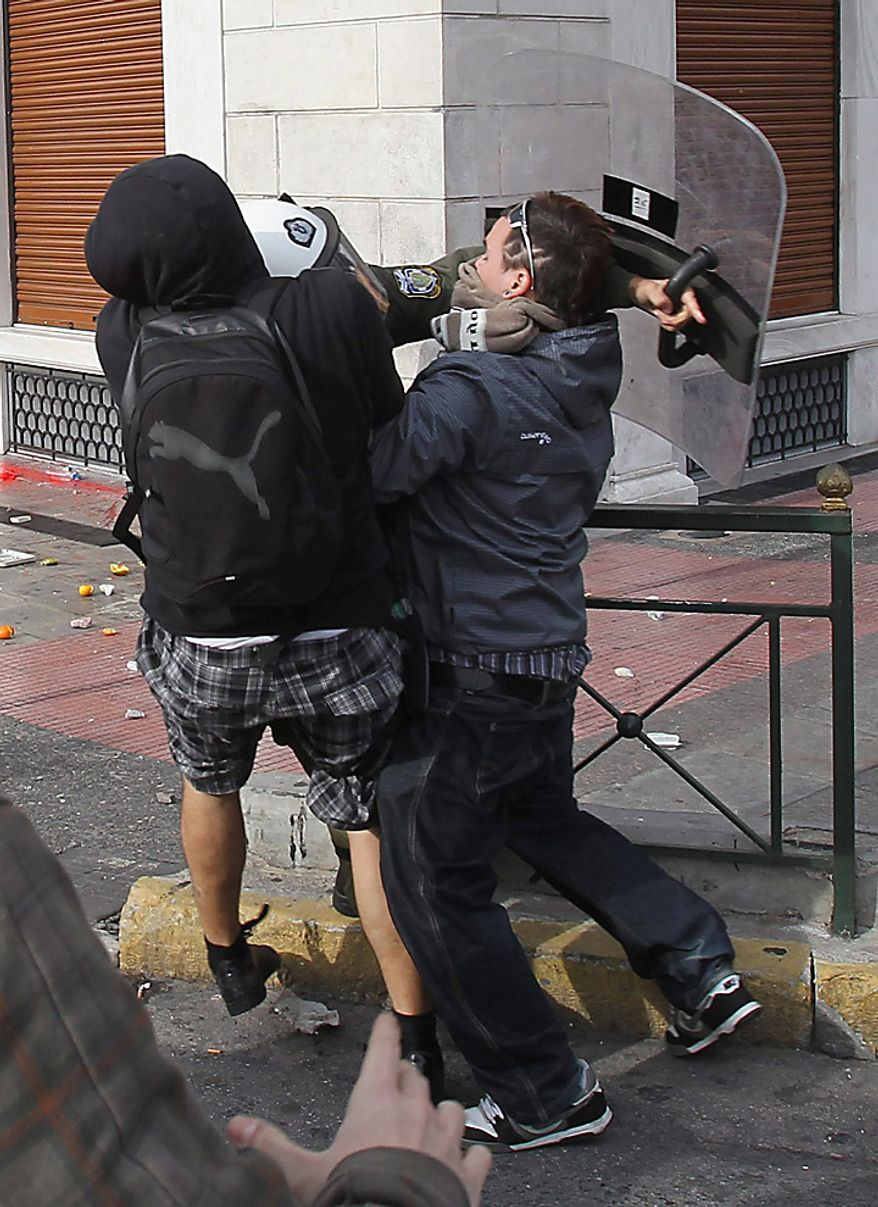 A youth with a bag attacks a riot police officer as another protester tries to restrain him during a rally in Athens on Monday, Dec. 6, 2010. Youths hurled rocks and oranges at a government building in central Athens during a student protest to mark two years since the fatal police shooting of a teenage boy that sparked Greece's worst riots in decades. Police closed roads and deployed several thousand officers around the city but maintained a minimal presence at the site where some 1,500 students gathered outside Athens University's main buildings. (AP Photo/Thanassis Stavrakis)