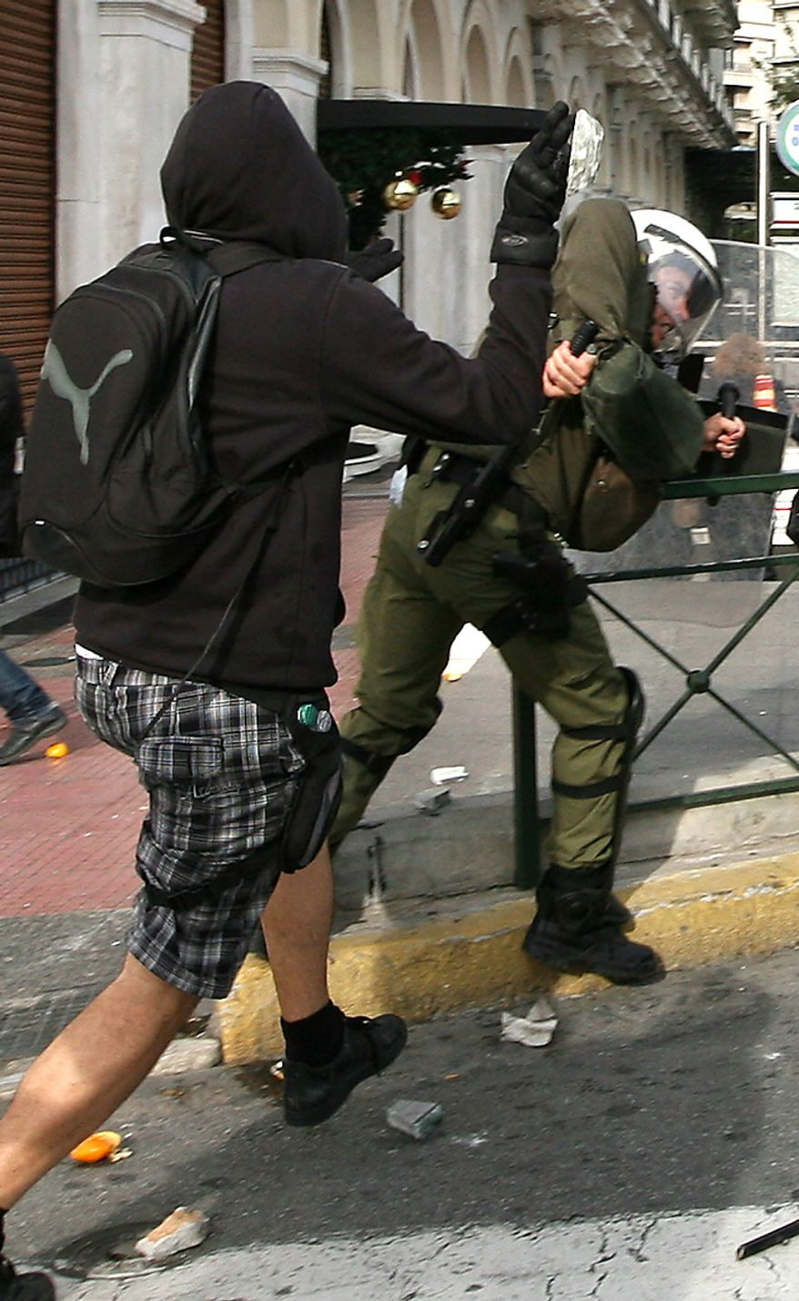 Protester attacks a riot police officer during a rally in Athens on Monday, Dec. 6, 2010. Youths hurled rocks and oranges at a government building in central Athens during a student protest to mark two years since the fatal police shooting of a teenage boy that sparked Greece's worst riots in decades. Police closed roads and deployed several thousand officers around the city but maintained a minimal presence at the site where some 1,500 students gathered outside Athens University's main buildings. (AP Photo/Alkis Konstantinidis)