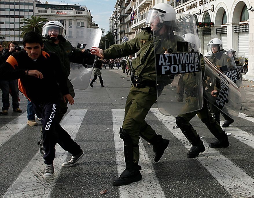 Protesters clash with riot police during a rally in Athens on Monday, Dec. 6, 2010. Youths hurled rocks and oranges at a government building in central Athens during a student protest to mark two years since the fatal police shooting of a teenage boy that sparked Greece's worst riots in decades. Police closed roads and deployed several thousand officers around the city but maintained a minimal presence at the site where some 1,500 students gathered outside Athens University's main buildings. (AP Photo/Alkis Konstantinidis)