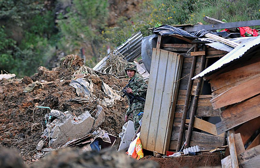 A soldier walks at the site where a landslide buried dozens of homes following weeks of drenching rains in Bello, northwestern Colombia, Sunday Dec. 5, 2010. The Red Cross attribute more than 180 deaths to heavy rains in Colombia so far this year. (AP Photo/Luis Benavides)