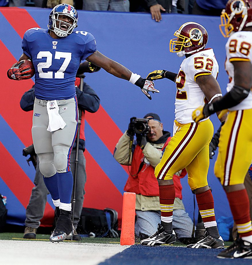 New York Giants running back Brandon Jacobs (27) celebrates after scoring a touchdown during the third quarter of an NFL football game as Washington Redskins linebacker Rocky McIntosh (52) and Brian Orakpo (98) look on at New Meadowlands Stadium, Sunday, Dec. 5, 2010, in East Rutherford, N.J. The Giants won the game 31-7. (AP Photo/Kathy Willens)