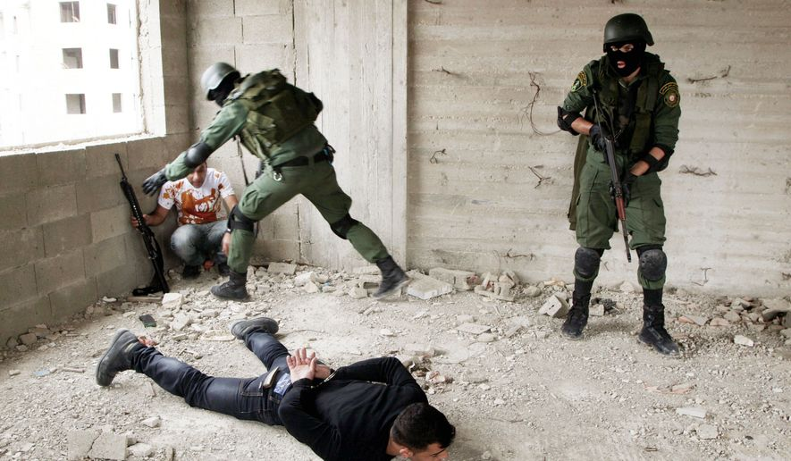 Palestinian security officers simulate an arrest during training in Nablus on Monday. The competence of Palestinian forces, many of them ex-militants, is considered a prerequisite for statehood. (Associated Press)